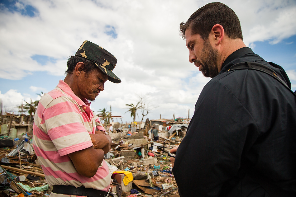 Rev. Ross Johnson, director of LCMS Disaster Response, prays with Tacloban resident John Lajara amongst the debris field in Tacloban City, Leyte province, Philippines on Tuesday, Nov. 19, 2013. Typhoon Haiyan caused widespread destruction, killing thousands and displacing millions of people. Photo by Erik M. Lunsford/LCMS