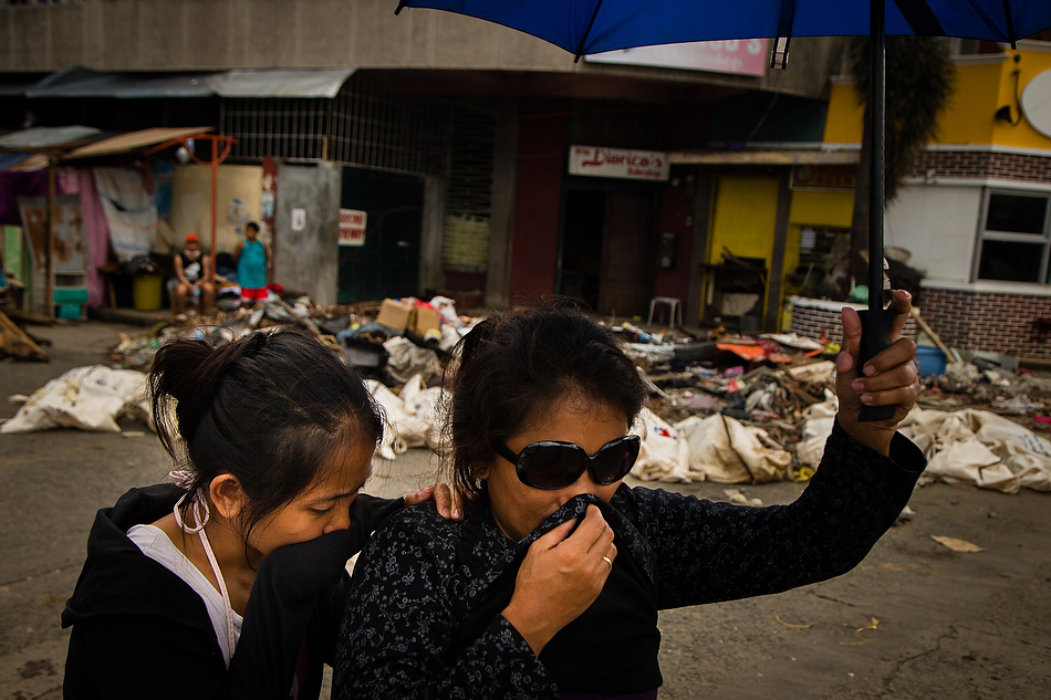 Residents of Tacloban City, Leyte province, Philippines cover their mouths as they pass dead bodies laying in the street on Tuesday, Nov. 19, 2013. Typhoon Haiyan caused widespread destruction, killing thousands and displacing millions. Photo by Erik M. Lunsford/LCMS