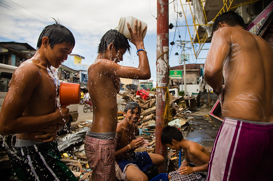 Boys shower and play amongst a street clogged by debris from Typhoon Haiyan in Tacloban City, Leyte province, Philippines on Monday, Nov. 19, 2013. Photo by Erik M. Lunsford/LCMS