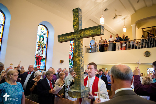 "The Rev. Jacob Mueller of Holy Cross Lutheran Church in Emma, Mo., carries the former steeple cross of St. John's Lutheran Church as crucifer before worship on Sunday, August 9, 2015, during a ""Day of Thanksgiving and Rededication"" at the church in New Minden, Ill. Nearly two years ago, a tornado damaged the church and surrounding homes, and toppled the cross, which was later placed next to the rededicated altar. A new steeple cross now adorns the church. LCMS Communications/Erik M. Lunsford"