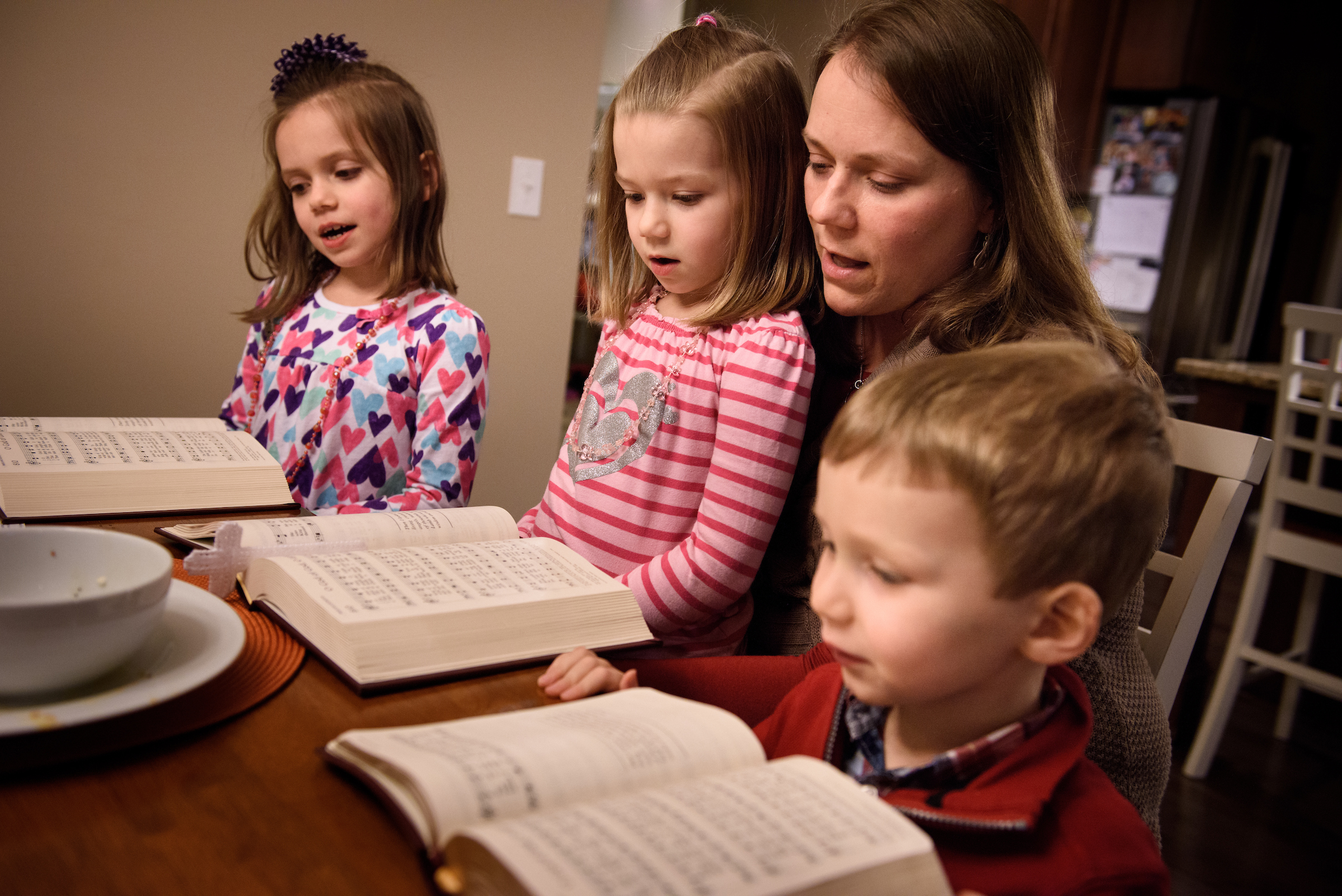 Laurie Vogt sings from the Lutheran Service Book with her children Elizabeth, Abigail (in lap) and Carl during an evening devotion with the Congregation at Prayer resource at their home on Sunday, Feb. 7, 2016, in Menomonee Falls, Wis. LCMS Communications/Erik M. Lunsford