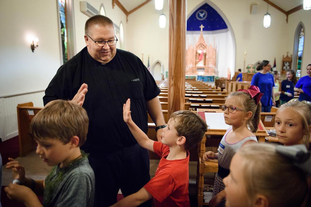 The Rev. David Daniel, pastor of Zion, high-fives campers at the end of the day. LCMS COMMUNICATIONS / ERIK LUNSFORD