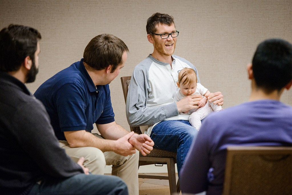 "Members of Rev. Andy and Nikki Becker's PALS group discuss their ministries Jan. 5 in St. Louis. From left are Revs. Michael Dobler, Daniel Maske, Jacob Hercamp (holding his daughter, Ella) and ""AJ"" Espinosa. (LCMS/Erik M. Lunsford)"