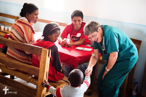 LaDonna Smith greets a new patient at the Mercy Medical Team clinic on Saturday, Oct. 18, 2014, at a Fiangonana Loterana Malagasy (FLM) Lutheran church in Antsoantany, Madagascar. Behind LaDonna is Solomona John Rakotonirina. LCMS Communications/Erik M. Lunsford