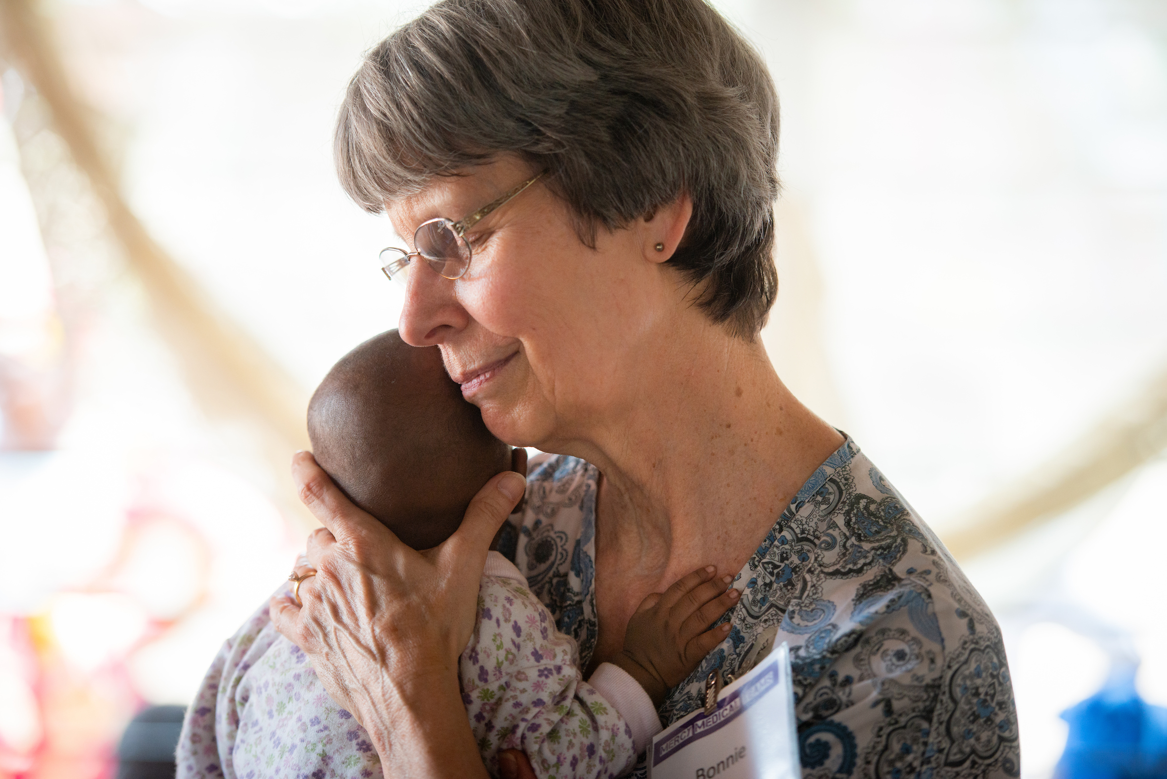 Bonnie Hartman, a member of Faith Lutheran Church, Godfrey, Ill., spends a few joyful moments holding an infant on the third day of the LCMS Mercy Medical Team on Wednesday, May 9, 2018, in the Yardu village outside Koidu, Sierra Leone, West Africa. LCMS Communications/Erik M. Lunsford