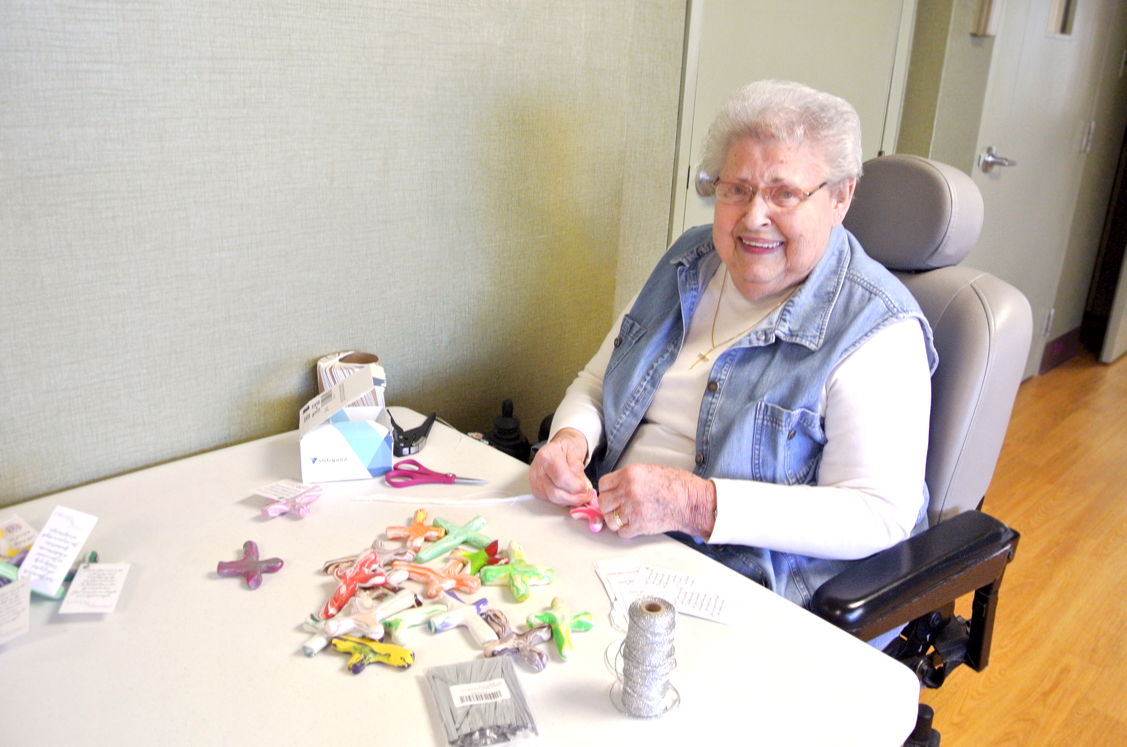 Perry Lutheran Home resident Virginia works on attaching tags with a Christian message to the prayer crosses. Used with permission / Perry Lutheran Home