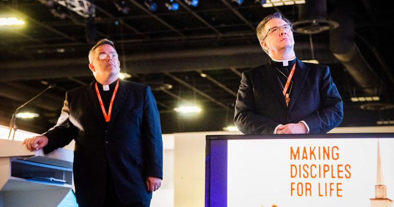 The Rev. Dr. R. Lee Hagan (left), chairman of Floor Committee 1 on National Witness, and the Rev. Christopher S. Esget, vice-chairman, join delegates in viewing a video on Making Disciples For Life, a new initiative of The Lutheran Church—Missouri Synod (LCMS). The video was part of the committee's July 21 presentation to the 67th Regular Convention of the LCMS in Tampa, Fla. (LCMS/Frank Kohn)