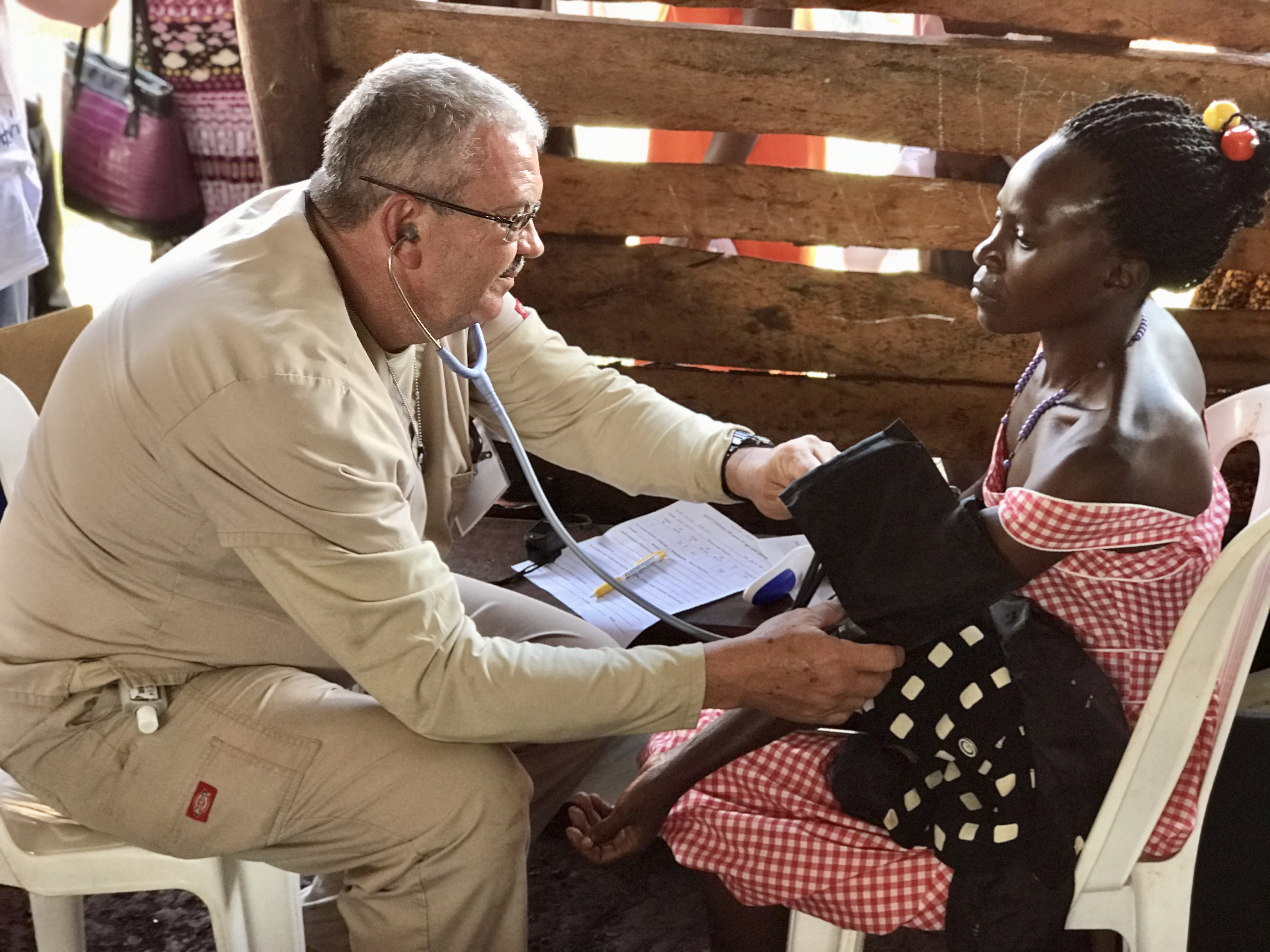 Ron Herman checks vital signs on a patient during the Mercy Medical Team trip to Uganda. Used with permission.