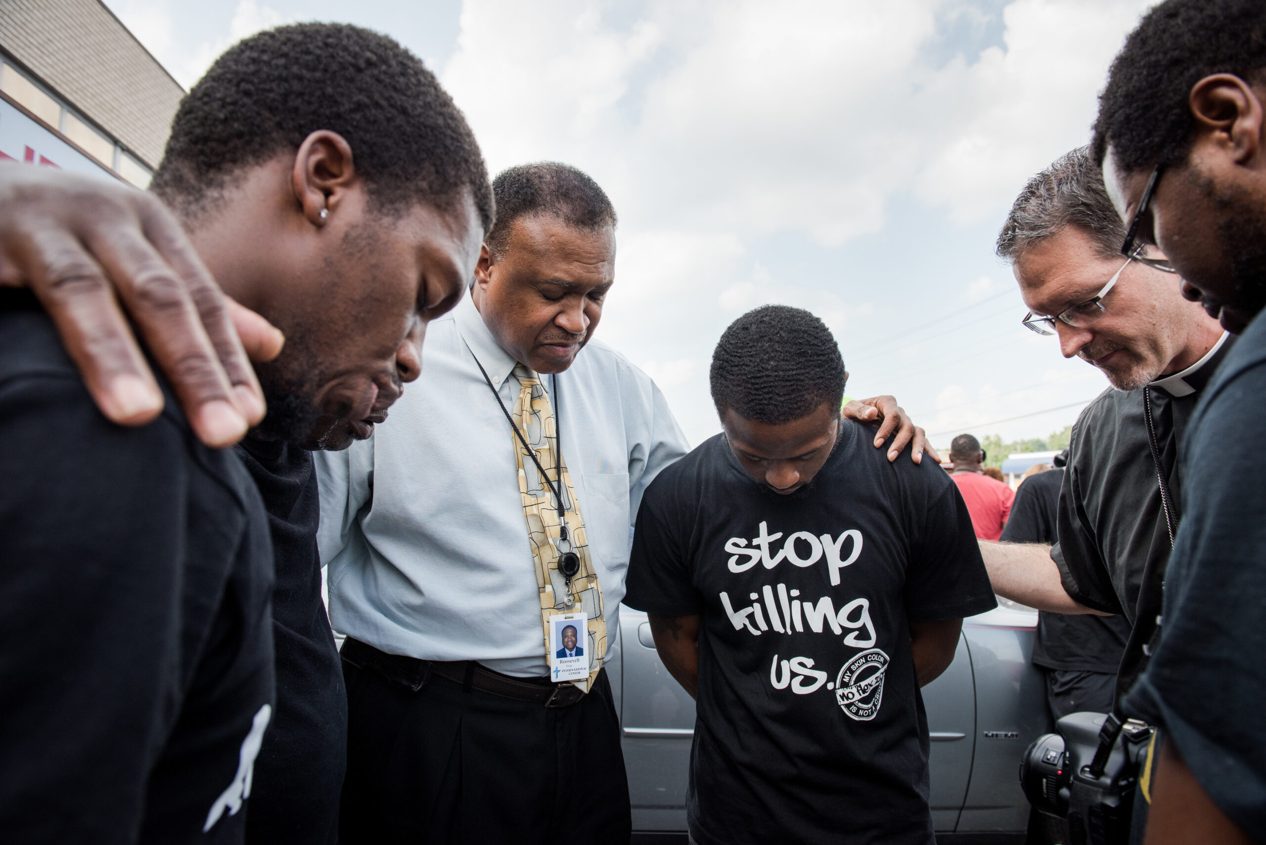 The Rev. Roosevelt Gray, director of LCMS Black Ministry (with tie), and the Rev. Steve Schave, director of LCMS Urban and Inner City Mission (second from right) pray with others along West Florissant Avenue on Monday, August 18, 2014, in Ferguson, Mo. LCMS Communications/Erik M. Lunsford